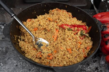 Fragrant delicious pilaf with garlic and pepper large. Street festive freshly prepared food. Delicious rice. Beautiful pilaf loose. Meat and rice. Garlic and hot pepper in the pilaf. Healthy food
