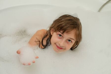 Young girl inside the bath. A little girl bathes in a bathtub with foam. A girl of 9 years old takes a bath. Purity concept Stock fotó - 138274025