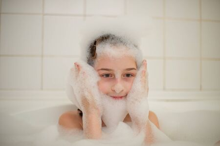 Young girl inside the bath. A little girl bathes in a bathtub with foam. A girl of 9 years old takes a bath. Purity concept