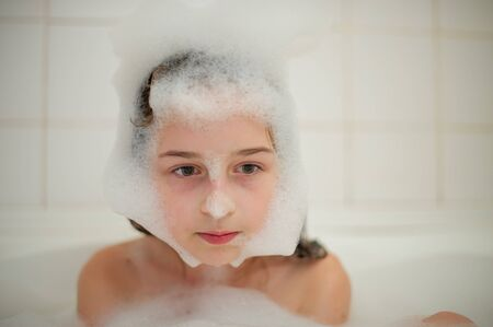 Young girl inside the bath. A little girl bathes in a bathtub with foam. A girl of 9 years old takes a bath. Purity concept Stock fotó - 138274059