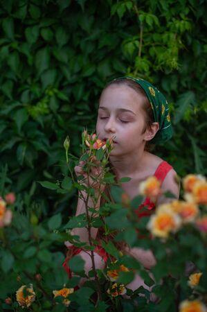 Petite fille dans la rue sur fond de feuillage vert. Fille aux cheveux longs. Enfant 9-10 ans fille en été.Fille 8-9 ans dans une robe orange et un foulard vert sur la tête.adolescente