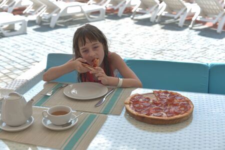 Portrait of young woman with pizza in cafe. Girl 9 years old eats pizza in a summer cafe on vacation. A girl of 9 years old has a rest in the summer and eats her lunch pizza with cheese. Water park