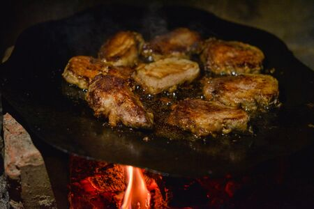 Cutlets pan fried in the fire. pan is also cooking meat. Pork chunks of meat are cooked on a bonfire on a disc from a harrow. Chunks of meat are fried with onions. Tasty dinner or lunch. Street food
