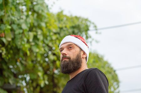 Santa Claus walking on city street. Man with a beard on the street in the summer in a hat of Santa Claus. A man with an emotional beard poses on a background of green foliage. New Year or Christmas