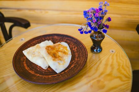 Pancakes to Maslenitsa celebration on the background of wooden boards. Pancakes on a brown plate in a cafe