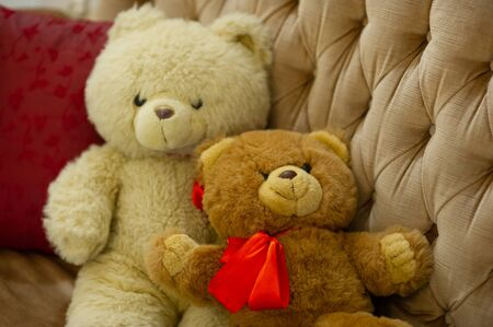 Relaxing time, two teddy bear friend sitting in the bed, vintage warm light filter, happy lovely teddy bear couple, together forever. 2 teddy bears. New Year or Christmas Teddy Bear. Toy on the couch