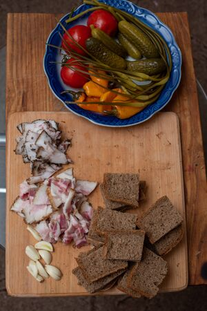 Bacon, bread and cucumber over wooden background. Russian and ukrainian traditional appetizer, Black bread lard pickles. Lard, tomatoes, pickles. Tasty appetizer with bacon