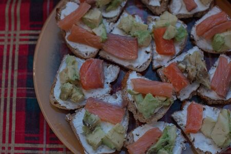 Toasts with avocado and smoked salmon. Sandwiches with Salmon and Avocado. Sandwiches with salmon and avocado and soft cheese on a plate on the table. Food photography.