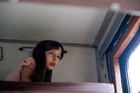 Cute girl lying on the top shelf in the train. Summer Vacation and Travel Concept. the girl in the train. A girl of 8 or 9 years old rides on a train. Girl makes selfie on a smartphone.