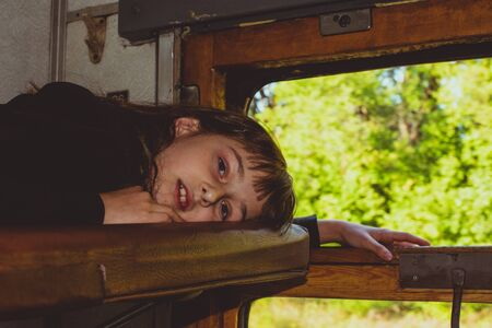 Tinted photo. Cute girl lying on the top shelf in the train. Summer Vacation and Travel Concept. the girl in the train lies on the top shelf. A girl of 8 or 9 years old rides on a train. Teen travels.