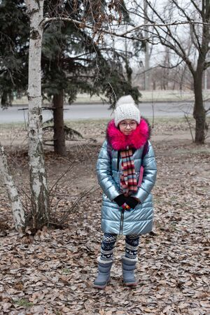 Close up portrait of a beautiful nine year old little girl in autumn park. 9 years old girl in a hat and a blue jacket. School child in winter clothes on the street. Beige hat. Girl 9 years old