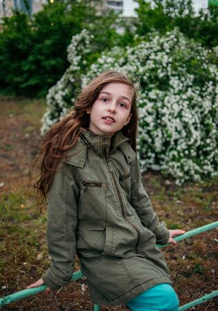 Little girl on the street against a background of green foliage.Girl with long hair. Child 9-10 years old girl.Girl 9 years old in the spring. A teenager in the spring on a walk. Military style jacket