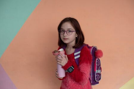 girl with cup. schoolgirl girl in glasses drinks water from a thermomug.A schoolgirl drinks tea, juice or water from a thermal cup or flask. girl at school drinks water or tea with a thermomug Banque d'images - 140092662