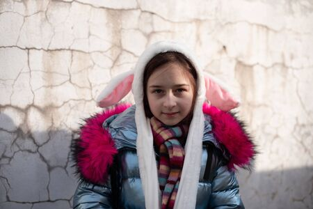 cute little girl in hood with ears. girl in a hat bunny street. Beautiful young cute woman in blue vegan and faux fur coat is posing on urban city background. Girl 9 years old. Eco clothing. Stock Photo