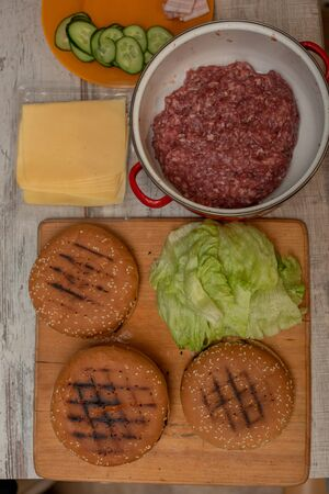 cooking hamburgers, making a hamburger, pictures with buns, raw meat, cheese and vegetables on the table. rolls and minced meat for making burgers and cheese. Iceberg lettuce leaves. Minced beef