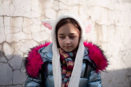cute little girl in hood with ears. girl in a hat bunny street. Beautiful young cute woman in blue vegan and faux fur coat is posing on urban city background. Girl 9 years old. Eco clothing.