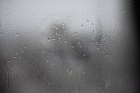The heart is painted on the misted glass in the winter. painted heart on wet glass Stock Photo