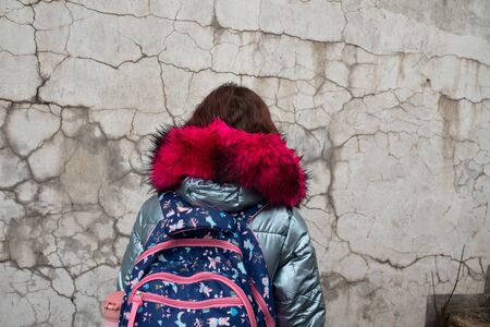 Girl in a winter jacket and a school backpack. Schoolgirl with backpack. Girl 9 years old with a school backpack on her back. Portrait of a schoolgirl 9 years old. 4th grade school.Girl on the street. Banque d'images - 140077286