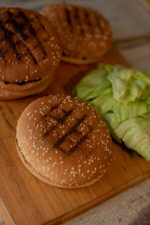 cooking hamburgers, making a hamburger, pictures with buns, vegetables on the table. rolls and minced meat for making burgers. Iceberg lettuce leaves. Burger rolls and iceberg lettuce 版權商用圖片