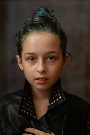 Portrait of nine year old girl. Teenager with blue strands on her hair. A series of photos of a girl of 8 or 9 years old. A teenage girl in a leather jacket. A teenager with collected hair in a bun. Reklamní fotografie