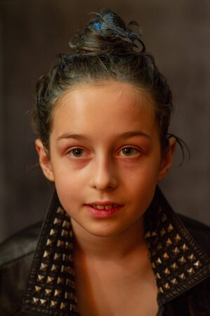 Portrait of nine year old girl. Teenager with blue strands on her hair. A series of photos of a girl of 8 or 9 years old. A teenage girl in a leather jacket. A teenager with collected hair in a bun. Stock fotó
