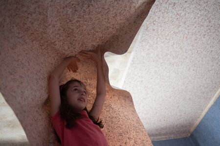 Woman hanging wallpaper motif. Teen girl helps to glue wallpaper on the ceiling. A girl of 9 years helps parents make repairs in the room. Help child. Teenager