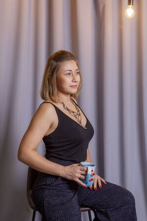 Business woman coffee cup hold. Girl with a cup on a gray background. Portrait of a girl. Woman in a black t-shirt on a gray background. Morning coffee or tea. Cute girl with a haircut Stock fotó
