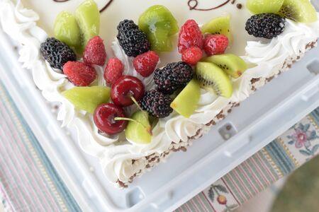 Fruit cake and whipped cream. Sponge cake covered with blackberries, raspberries, kiwi, cherries. Blackberry fruit cake raspberry cherry kiwi. Food photography. Sweetness Fruit Pie. Tea sweets Stockfoto