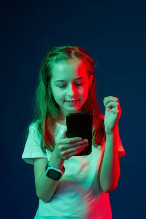 Teenager talking on the smartphone. The girl with a smartphone in the hands of. Girl with a smartphone in the hands of a red green filter. Smartwatch A 9 year old girl photographs herself on the phone Stock fotó