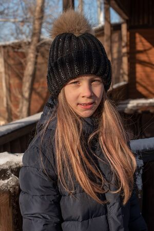 portrait of a beautiful blonde in a hat on the background of the city landscape in the cold season. girl walking down the street. Girl in a black hat and blue down jacket in winter. Girl 9 years old. Stock fotó
