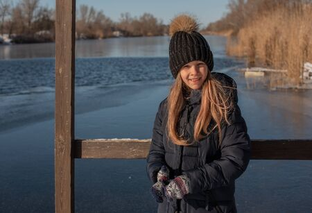 girl on the background of winter lake or river. landscape with frozen lake. winter season. Girl in winter clothes on a background of the river. Girl 9 years old against the background of a small river