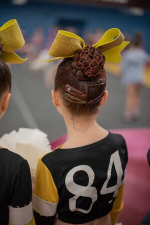 Cheerleader. cheerleader girl of 9 years in anticipation of a sports performance. The girl is a sporewoman.A child worries before going on stage for a cheerleading or acrobatics competition.Gymnastics