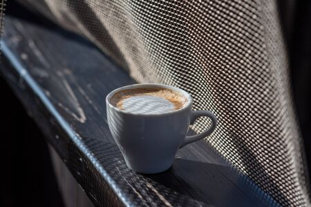 Coffee selective focus. White cup with cappuccino on the nature. White cup with cappuccino, coffee, morning, cheerfulness.