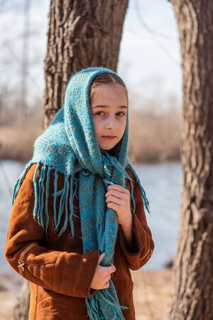 A girl in a light sheepskin coat stands on the bank of the river on a sunny day. Girl 9 years old in a sheepskin coat by the river. Girl 9 years old or 10 years old. Nature, child, schoolgirl.Teenager