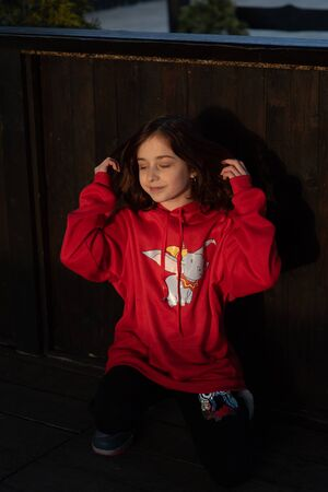 Close up portrait of a beautiful nine year old little girl. Portrait of happy, smiling, confident 9 years old girl. Teenager in a red sweatshirt on a wooden background. Girl with red hair.