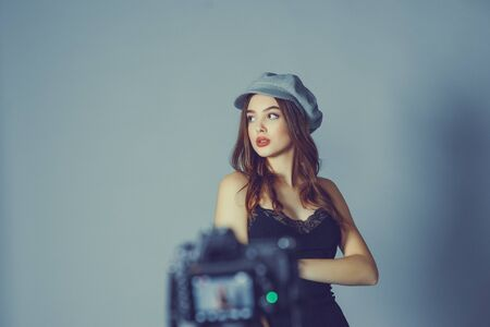 Glamorous young woman wears fashionable dress posing with fluttering hair at grey wall.Girl put forward hand in a black dress and a gray cap.A girl is photographed on a camera or I am shooting a video