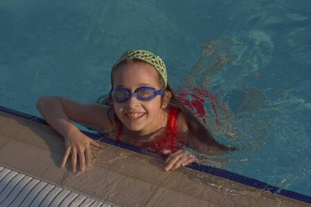 Cute girl with goggles in swimming pool. Girl swims in the pool with goggles. Summer, pool, relaxation, water park, relaxation area. The baby is swimming. Hello summer. Hooray, holidays. health