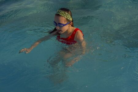 Cute girl with goggles in swimming pool. Girl swims in the pool with goggles. Summer, pool, relaxation, water park, relaxation area. The baby is swimming. Hello summer. Hooray, holidays. health Stok Fotoğraf