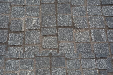 old European courtyard, paved with gray cobblestones. Pavers texture. A perspective view of the monotonous gray brick stone pavement on the ground for Street Road. Sidewalk, driveway, pavers