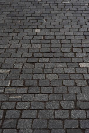 old European courtyard, paved with gray cobblestones. Pavers texture. A perspective view of the monotonous gray brick stone pavement on the ground for Street Road. Sidewalk, driveway, pavers Standard-Bild