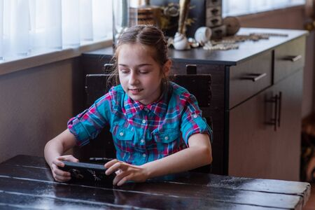 The Internet. Message. Girl in a cafe with a smartphone. The child looks in the smartphone. Gadgets and kids. A teenager runs his video blog. A blogger is looking at his gadget. Girl 9 years old.
