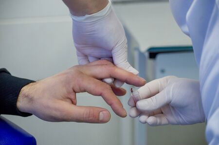 Man gives blood. Blood is taken from a man for analysis from a finger in a specialized medical laboratory. Treatment, virus, health. The concept of medicine, people's health. Finger blood, test tube Standard-Bild