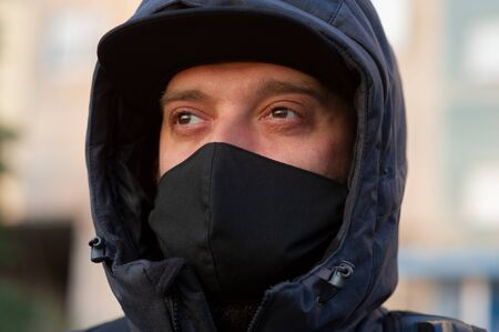 A man wearing a black respiratory mask on his face. A man in the street in a black mask. Virus. Coronavirus. A guy in the spring on the street in a respiratory mask to protect against infection virus