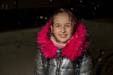portrait of a beautiful nine year old little girl. 9 years old girl in a blue jacket. School child in winter. Teenager. Winter and snow. Snowy evening. The child enjoys the snow. Jacket with eco-fur