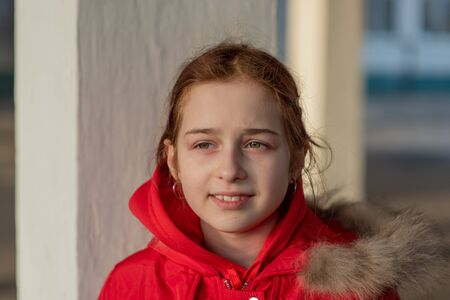Close up portrait of a beautiful nine year old little girl. School child in winter clothes. Girl 9 years old. Teenager, portrait. Girl in a red jacket. New generation. the children of the Z-generation