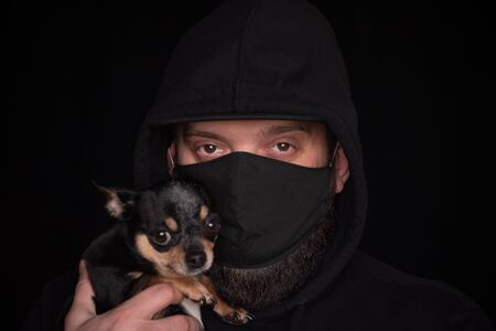 Coronavirus.Man in protective surgical mask.Coronavirus disease COVID-19 is dangerous for pets.Masked man with a dog. Chihuahua and a masked man. Health, bacteria, protection.Guy on a black background Stock Photo