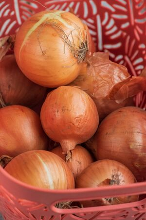onion. Onions in a basket. Large onion harvest in a basket. Bulb onion is rich in vitamins, useful spring. Onion peel on a wooden background. Large onions can be seen from above.Raw onions in a basket