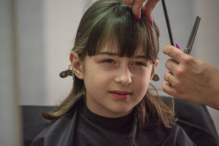 hair salon concept. Girl bang bang in a beauty salon. A child in the barber cuts his hair.