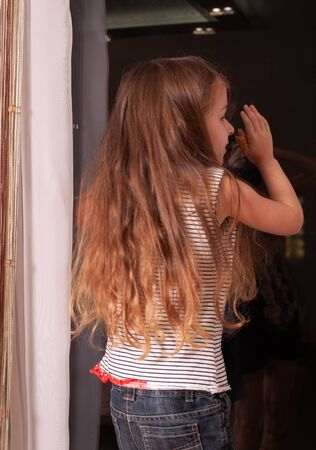 little girl looking out window while standing on windowsill. Portrait of a little girl who stands on the windowsill. Banque d'images