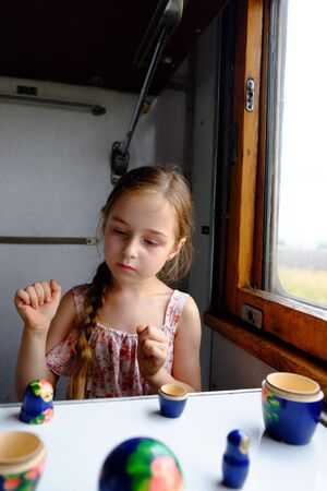 Cute girl in the train. Summer Vacation and Travel Concept. A girl of 5 or 6 years old rides on a train. Teen travels. Little girl with long hair. Child portrait